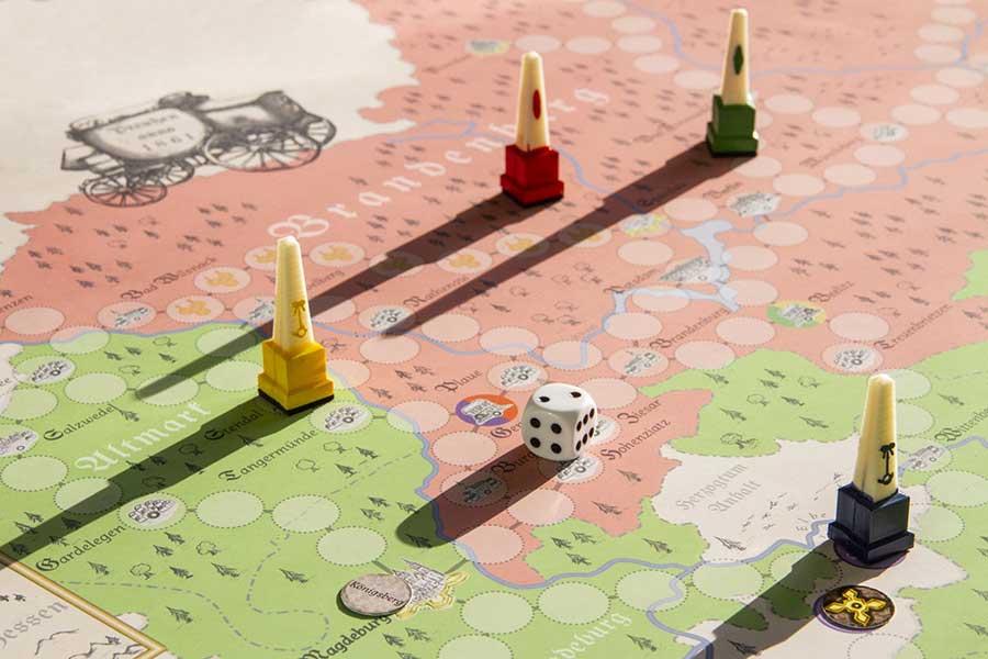 Spielfiguren, Spielbrett und Würfel. Foto: Ausbildung/LGB geobasis-bb.de